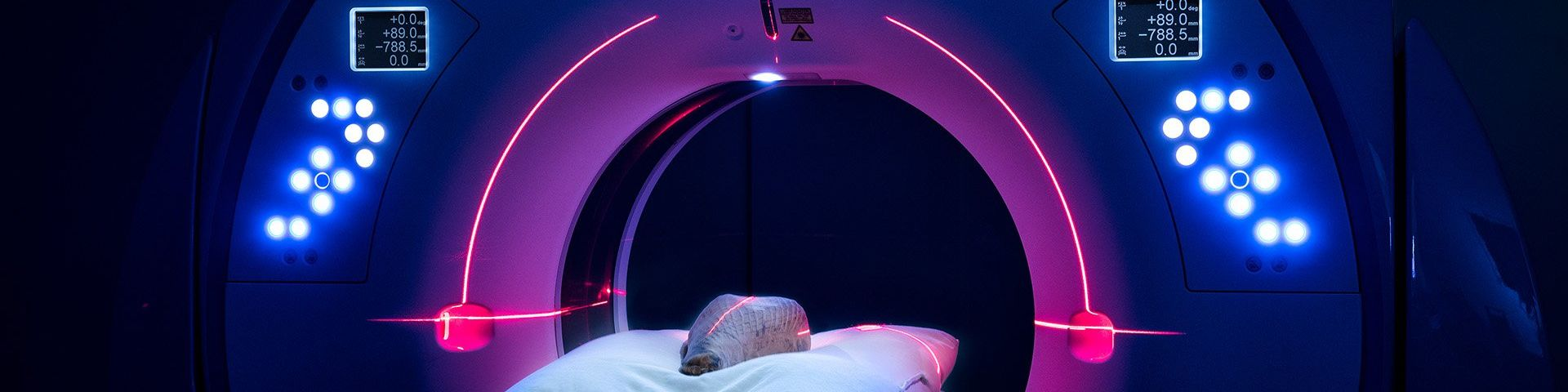 An object lies on a bed, inside a round CT scanner. It is illuminated with blue and purple lights.